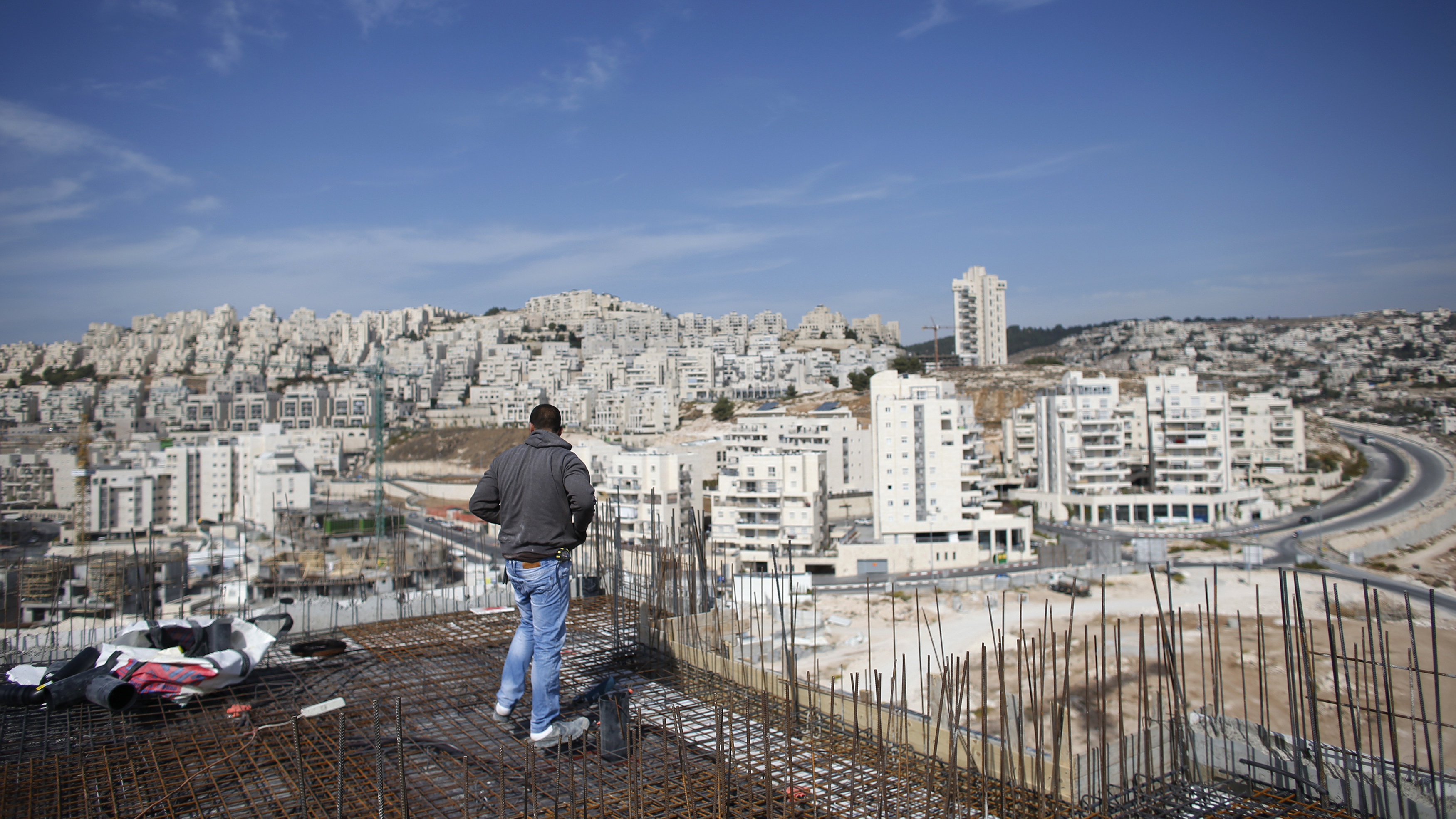 A labourer stands on an apartment building under construction in a Jewish settlement known to Israelis as Har Homa and to Palestinians as Jabal Abu Ghneim, in an area of the West Bank that Israel captured in a 1967 war and annexed to the city of Jerusalem, October 28, 2014. REUTERS/Ronen Zvulun
